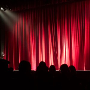 Stage with red curtains and audience watching.